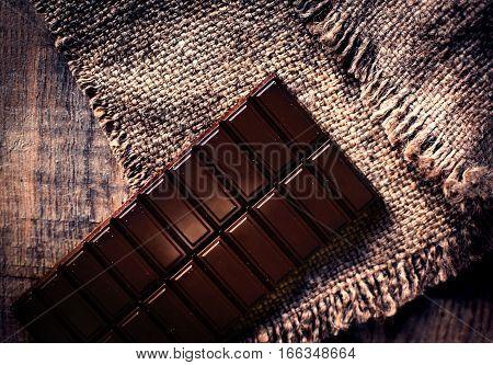 Dark Chocolate bar on dark old wooden background
