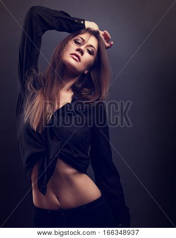 Female Slim Model Posing In Black Shirt With Long Hair And Looking Sexy On Dark Background. Fashion