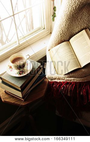 Early Morning Coffee. Beautiful antique teacup on old book pile. Open book, cozy blanket on chair.