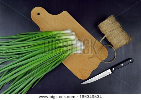 A bunch of fresh chives on a wooden cutting board. Spring. Vitamins. Cooking. Fresh organic produce. Green onions. Kitchen tools. Rural atmosphere.Food background.