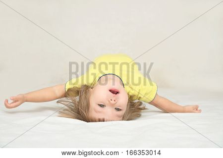 Little girl having fun lying on back spine back bend bridge figure happy smiling child happiness childhood concept