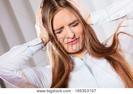 Stressful situations in work. Headache and migraine. Young woman in office pain and emotions.