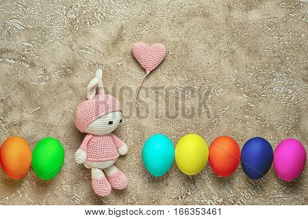 Amigurumi toy easter bunny bunny and crocheted heart shaped balloon with colorful eggs in a row - easter background with copy space