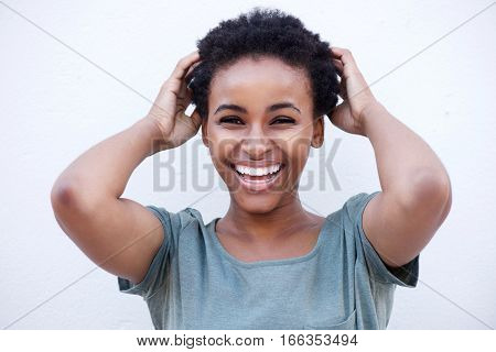 Young Woman Laughing With Hands In Hair Against White Background