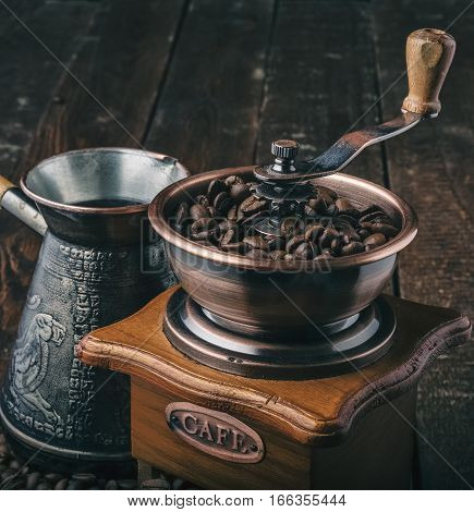 Close up vintage coffee grinder with beans and jezve on dark background