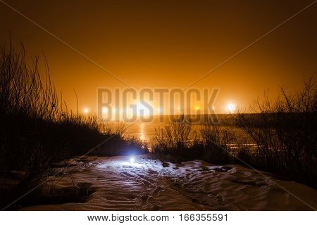 Night winter landscape with the river in the light of the full moon