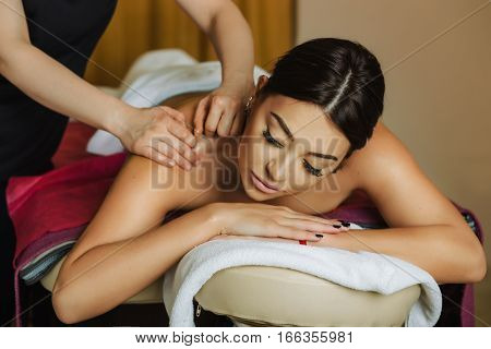 beautiful and healthy woman lying on a massage table receiving back massage in spa salon . Traditional massage therapy and spa treatment.