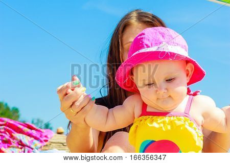 Woman and child posing in swimsuit on sunny day