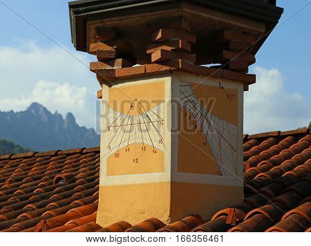 ancient sundial with hour numbers on the chimney of a house facing south west poster