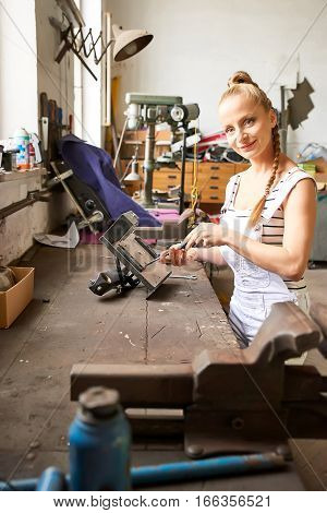 A young woman working at the table using a screwdriver in a workshop.