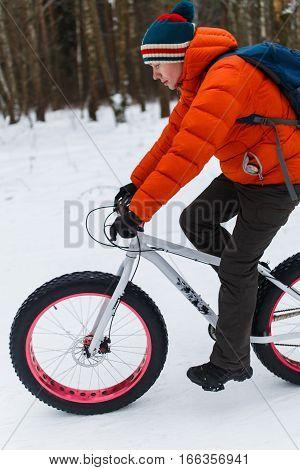 Man riding on sports bike in winter wood