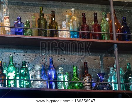 A lot of different colored glass bottles on shelves.