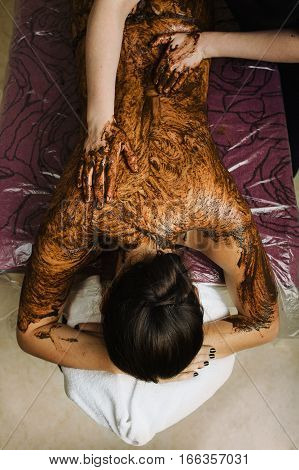 Spa therapist doing back massage on woman body using coffee peeling in the spa salon. Procedure for recovery and cleansing skin, top view