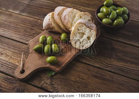 Green olives on a wooden board ciabatta on wooden background. Ciabatta. Sliced ciabatta