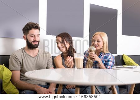 Friends siting and talking at a table in a coffee shop.