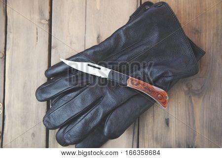 knife on black gloves on wooden table