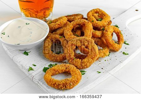 Fried Breaded Onion Rings with sauce and Light Beer on white wooden board, background