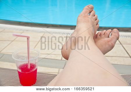 Relax by the pool - point of view photo of legs and drink