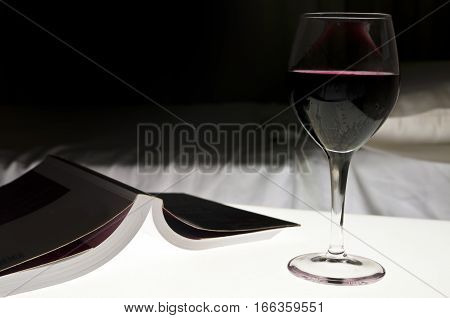 Book red wine next to a bed. Evening relax concept.