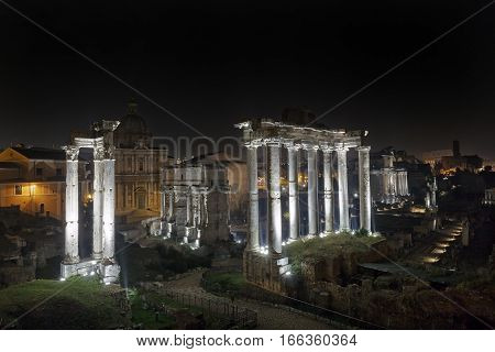 The Roman Forum photographed at night with artificial lights. The Roman Forum: in the foreground the Temple of Saturn to the left of the Arch of Septimius Severus.
