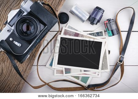 Stack of photos and old camera on wooden background