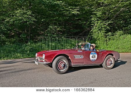 PASSO DELLA FUTA (FI) ITALY - MAY 21: driver and co-driver on a classic German car BMW 507 (1957) travel in Tuscany during the historical race Mille Miglia on May 21, 2016 in Passo della Futa (FI) Italy