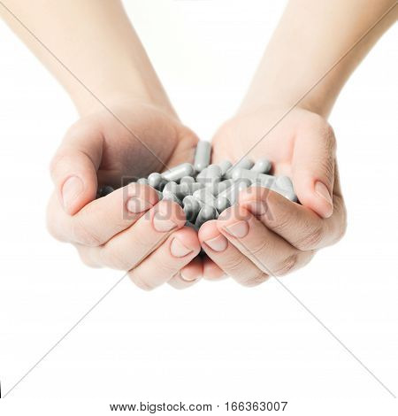 Hands Is Giving Gray Capsules Pills On White Background. Health Care Concept