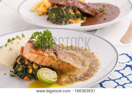 A nice dish of salmon and beef steak served with mashed potato,lemon, saute spinach and sauce on background with wooden utensils.