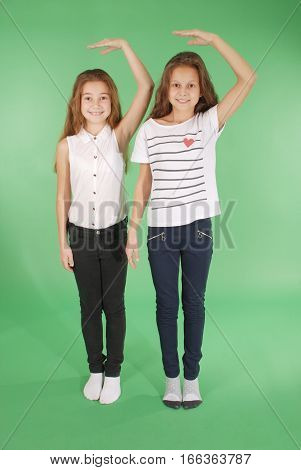 Two school girls hold hands above head and measuring his growth isolated on green