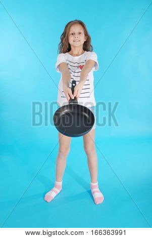 Young girl with a frying pan isolated on blue background