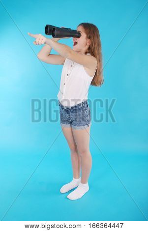 Beautiful young girl looking through binoculars with surprised expression. Isolated on blue