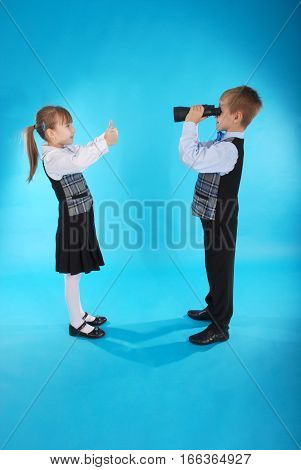 Schoolboy and schoolgirl playing with binoculars. Photos on a blue background