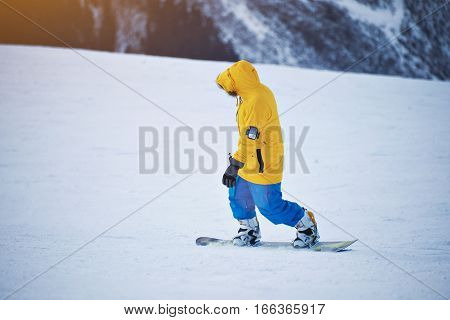 Snowboarder in bright yellow jacket and blue pants rides down on snow slope at sunny winer day in mountain ski resort
