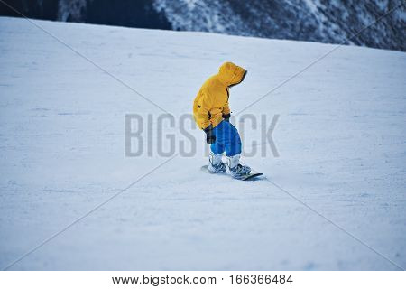 Snowboarder in bright yellow parka and blue pants looks down on snow slope before start to ride at sunny winer day in mountain ski resort