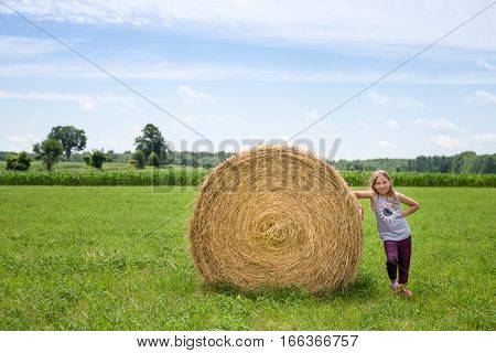 Young girl standing next to a hay bale in a green field. Warm light with copy space in sky if needed. Concepts could include healthy lifestyle agriculture nature others.