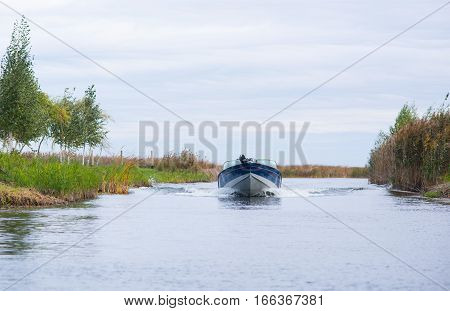 Aluminum Motor boat on a lake on a sky background