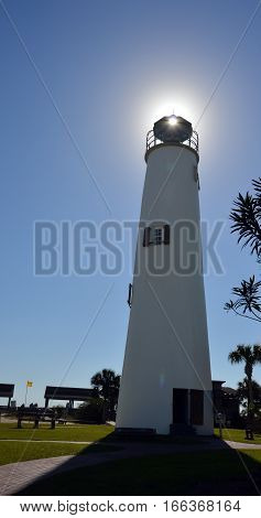 A photo of a lighthouse with the sun shinning through the lens