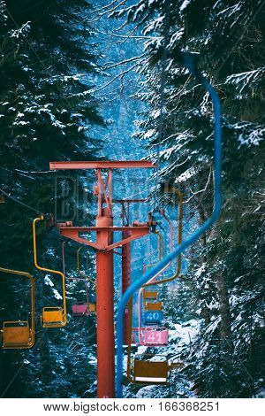 Vertical shot of vintage grunge ski lift with pastel colored chairs, moving through winter pine forest covered in fresh snow in mountains