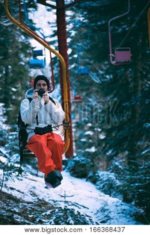 Young snowboarder man, sitting in small ski lift chair, moves through winter forest and takes photo with his small pocket camera or smartphone