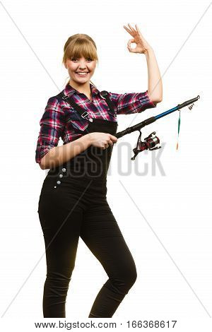 Fishing concept. Attractive woman in dungarees pink check shirt showing holding rod a ok gesture. Isolated background