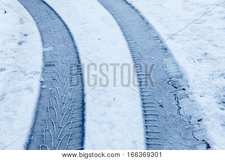 Curved car tracks in the snow closeup