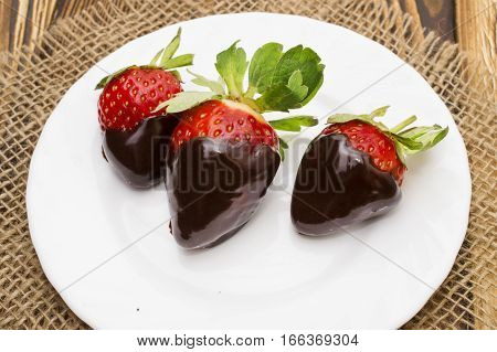berry ripe strawberries in chocolate on a wooden background