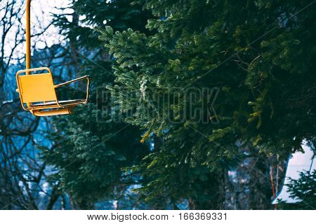 Stylistic photo of old vintage grunged yellow empty ski lift chair isolated on left, bahinf pine tree branches in winter forest, focus on seat