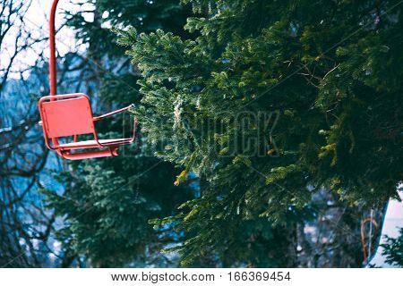 Stylistic photo of old vintage grunged red empty ski lift chair isolated on left, bahinf pine tree branches in winter forest, focus on tree