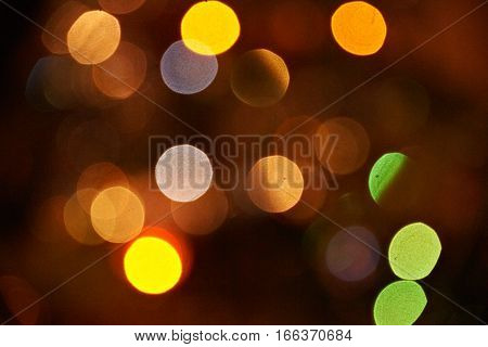 Close shot of warm big orange, yellow, green boheh light spots. Holiday abstract background