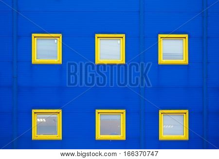 Facade of a modern blue warehouse and six yellow windows.