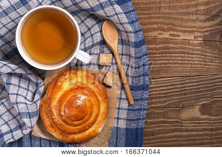 Cup of tea and sweet bun for breakfast on wooden table top view