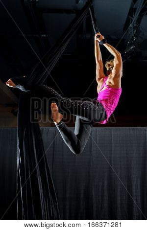 The back of a muscular aerialist as she hangs from a silk in a belay loop stag pose. She is very fit and wearing work out clothes.