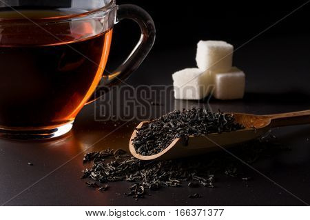 tea strainer with a tea cup on a dark background.