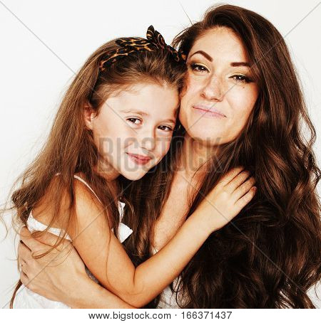 young mother with little cute daughter emotional posing on white, happy smiling family inside isolated adorable, lifestyle people concept close up